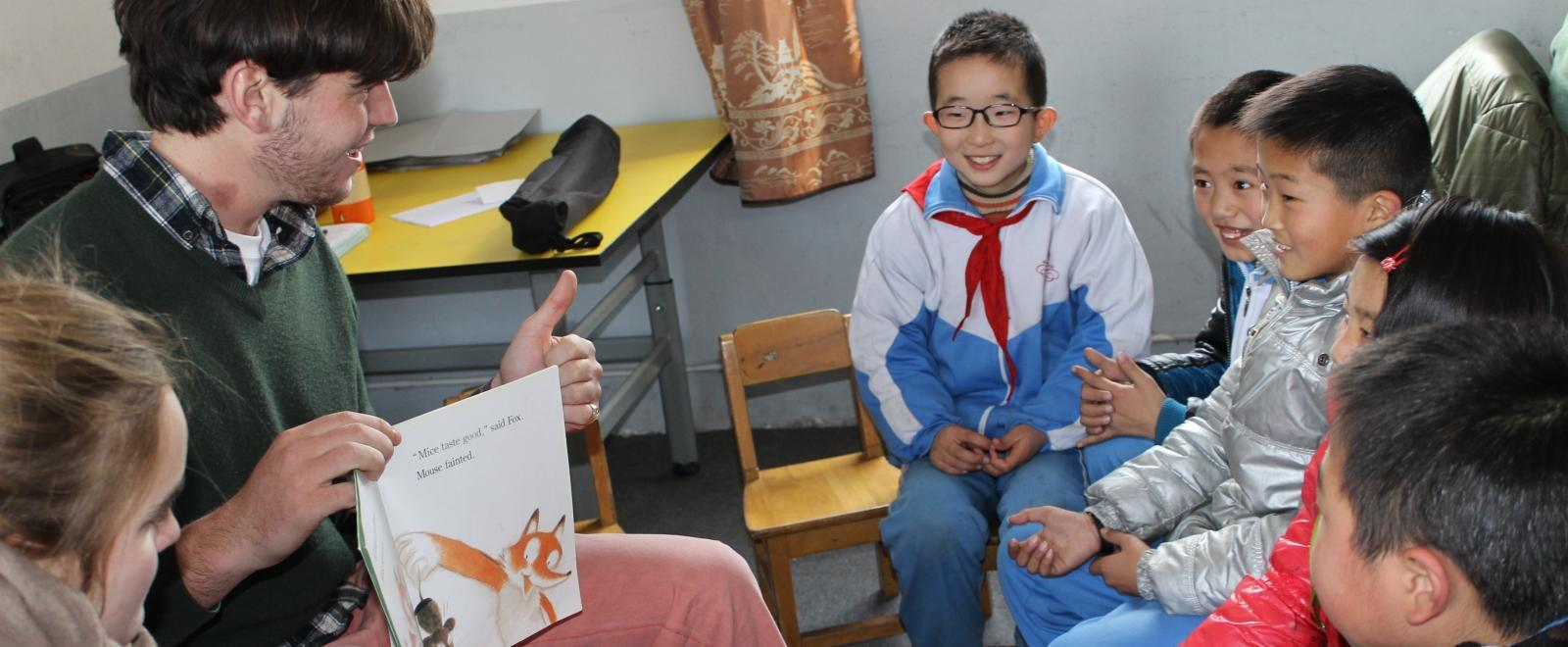 A volunteer reads a book to his students during his teaching work experience in China